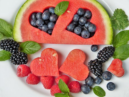 Watermelon with two heart shaped sections cut out lying next to assorted berries on a plate to make healthy food fun for children