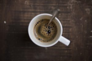 Black coffee in a white mug with a spoon as list of healthy foods