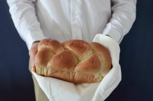 Chef holding a freshly bakes white loaf on a white tea towel