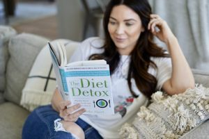 Woman sitting on sofa reading a diet book