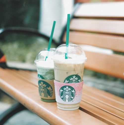 Two Starbucks cups filled with flavoured coffee left on a park bench by dentists Glasgow